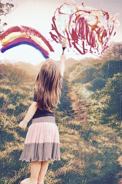 空中にカラフルな絵の具で絵を描く少女