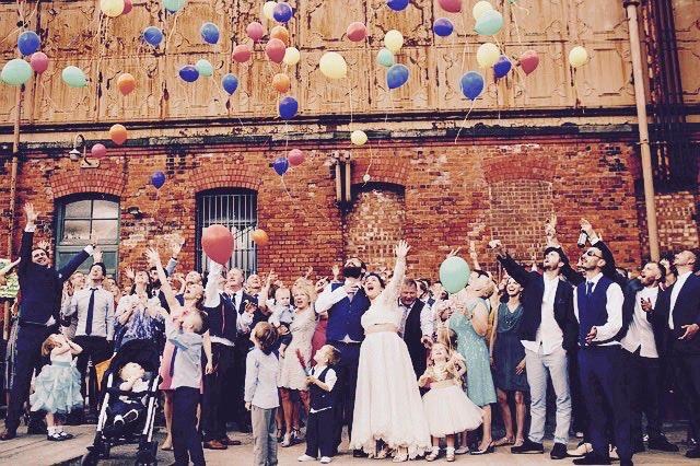 カラフルな風船を見上げる幸せそうな結婚式の参列者たち