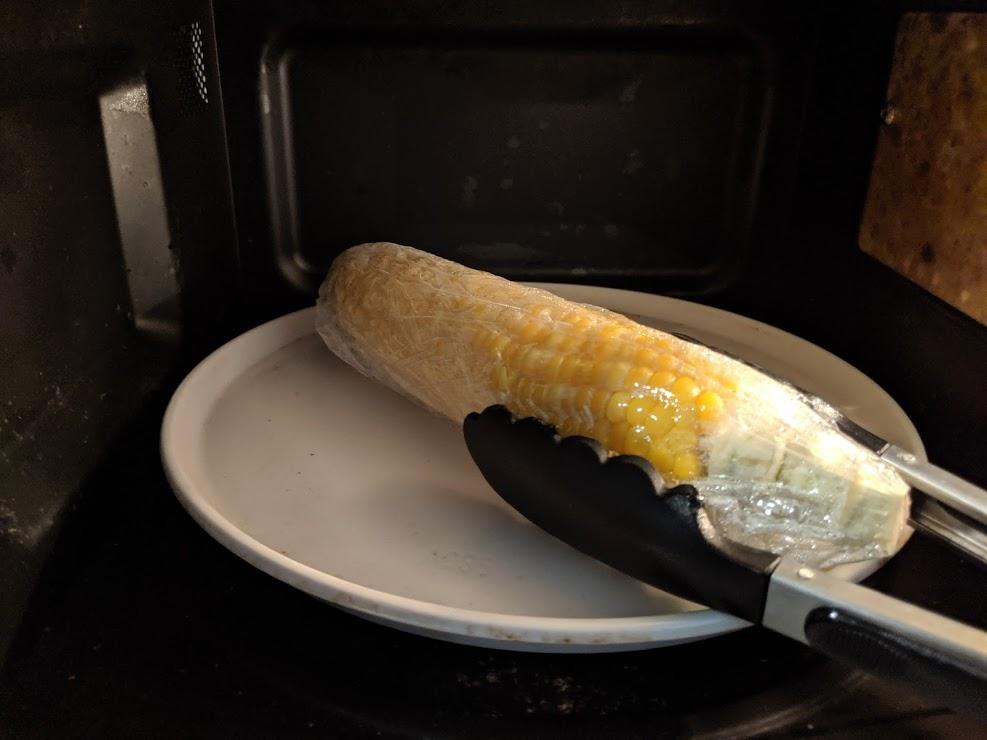 トングを使ってトウモコロシをひっくり返す