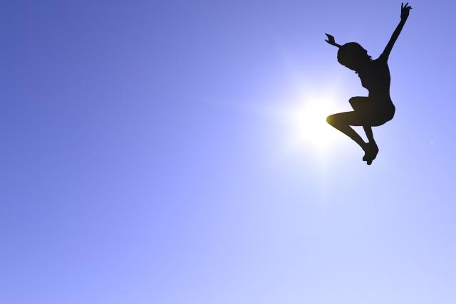 高く飛び喜ぶシルエット
