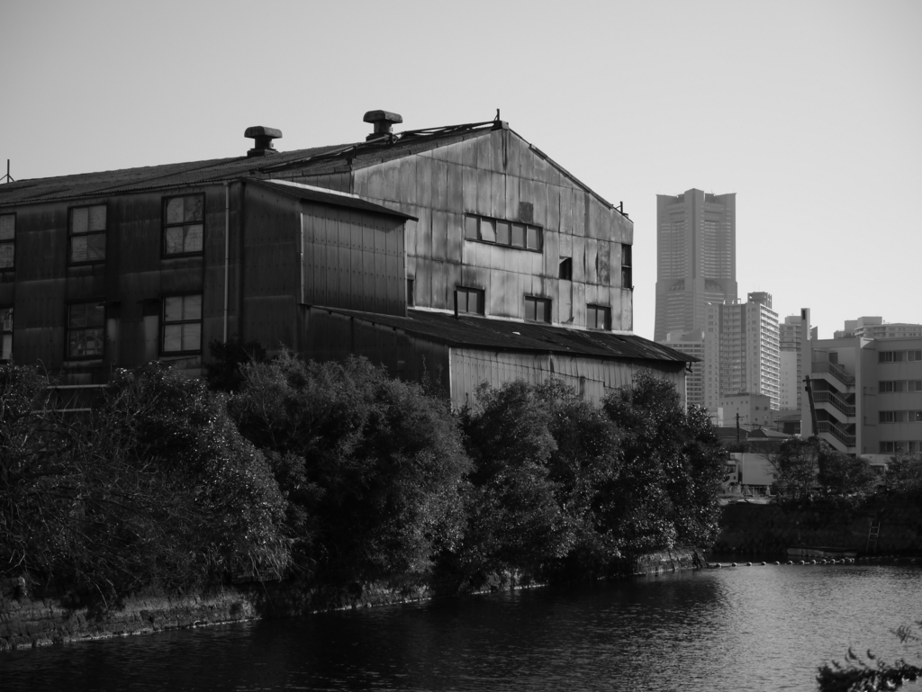 ランドマークタワーを背景に古工場をモノクロで