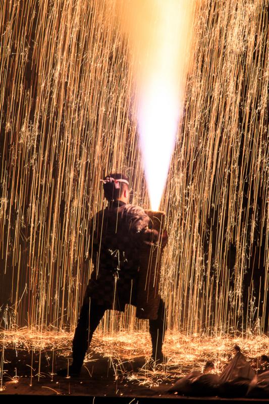 手筒花火を持つ男の背中