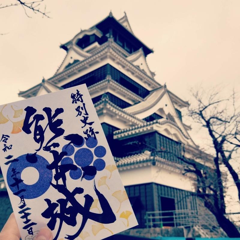 熊本城を背景に撮った熊本城の季節限定の銀杏のデザインの御城印の写真