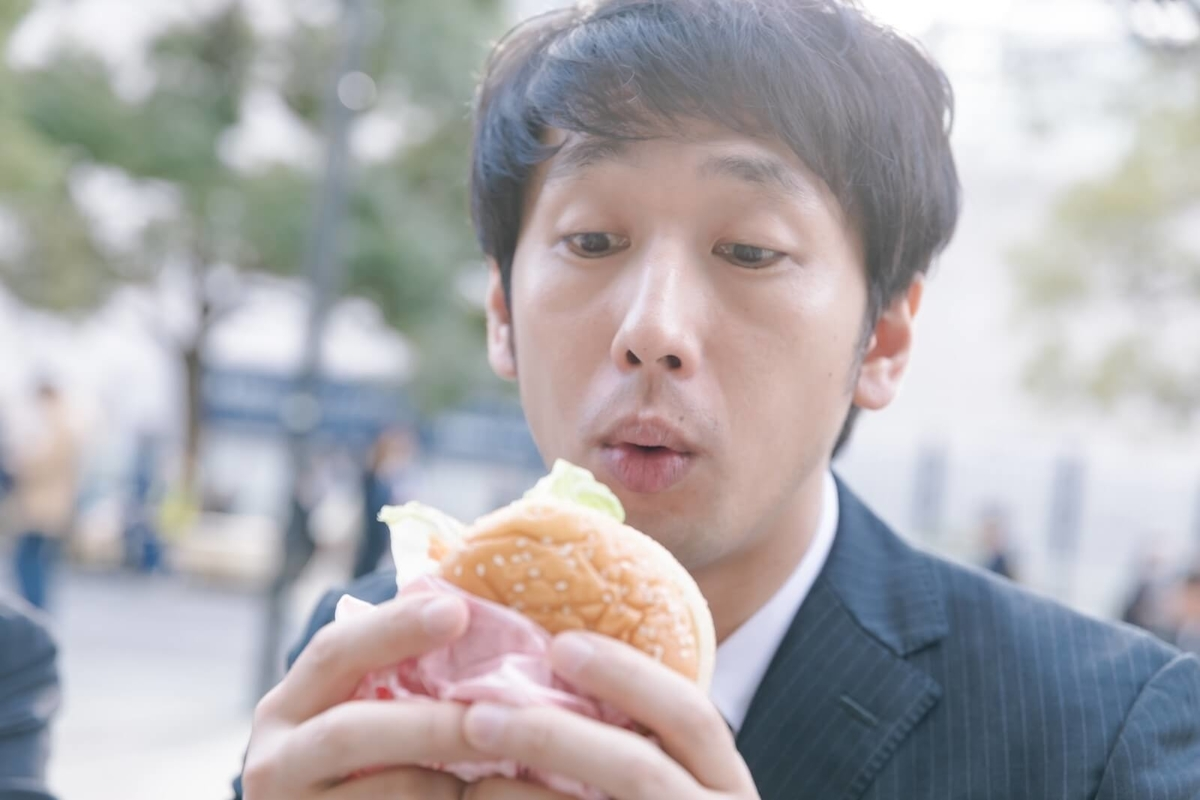 ハンバーガーを疑心暗鬼に見つめる男性