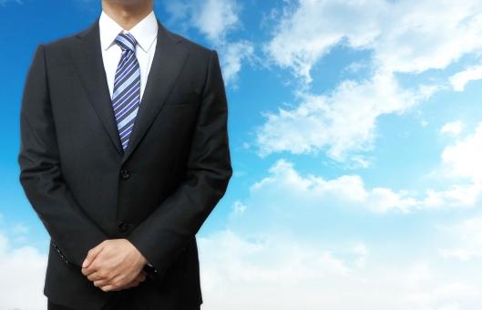 スーツ姿の男性と青空