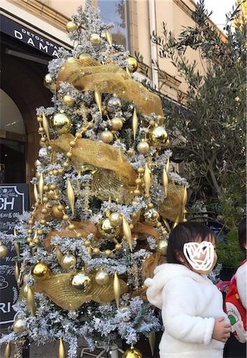 クリスマスツリーの前で立つ子供