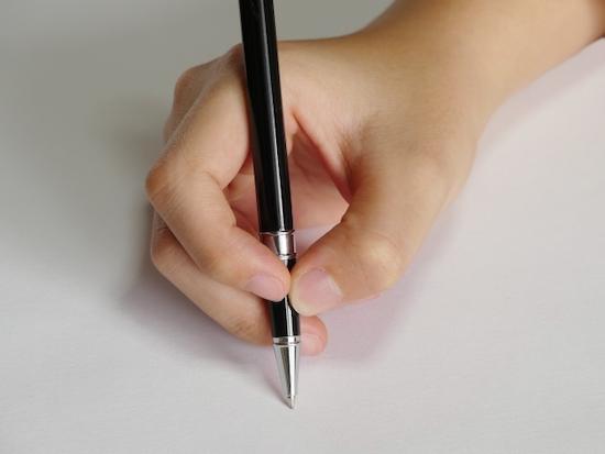 ペンを握る手の写真