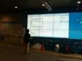 大きなWindowsの画面、前にいるおっちゃんがワイアレスで操作