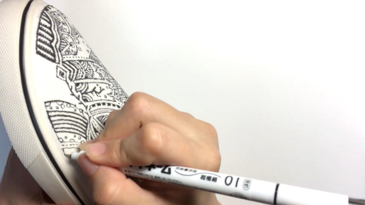 スリッポンに細かい模様を描いているシーン