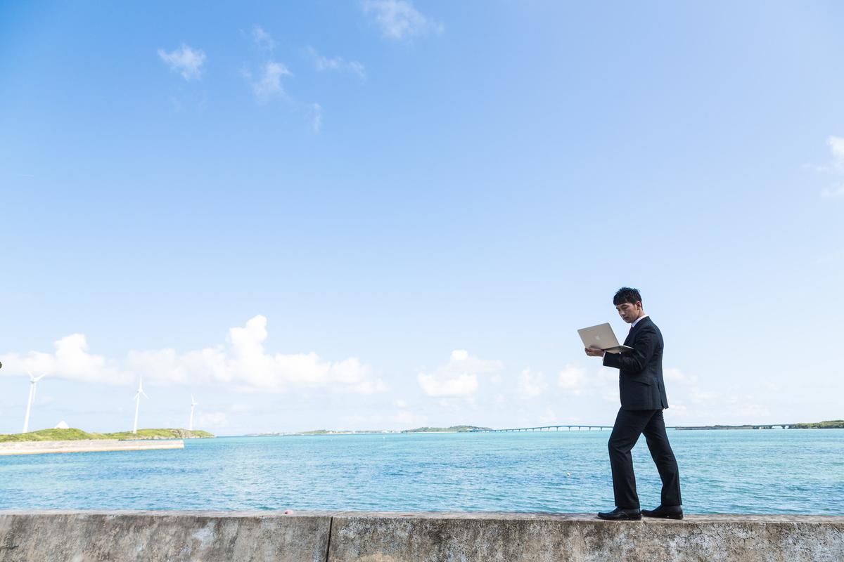 堤防の上で仕事をするビジネスマン