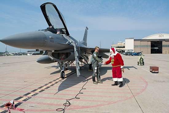 戦闘機の前で握手するサンタと隊員