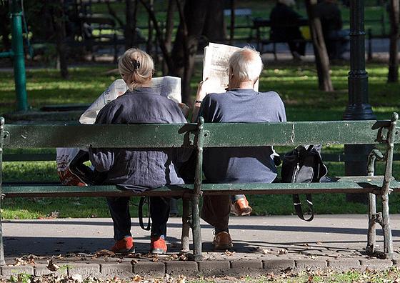 新聞を読み比べする老夫婦