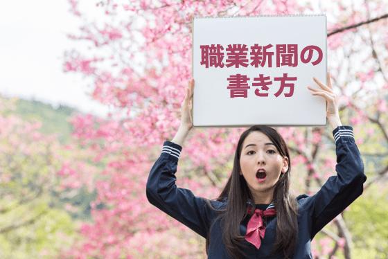 職業新聞の書き方のプレートを掲げる女子中学生