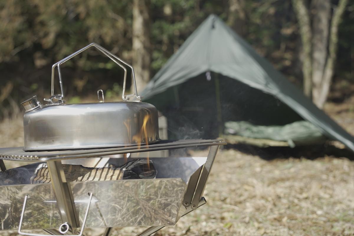 ケトルがメインに写っているキャンプの写真