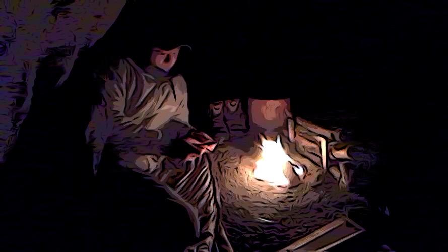 夜に横になりながら焚き火に当たっている様子