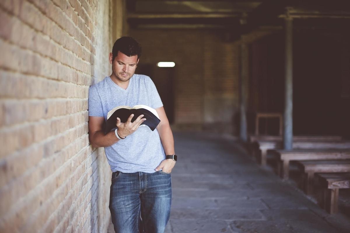 壁に寄りかかって本を読む男性