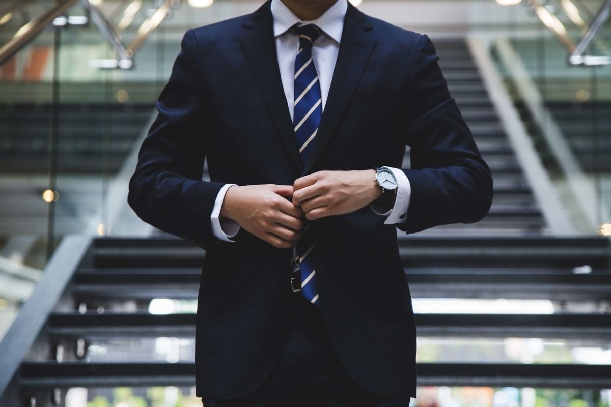 スーツのボタンを結ぶ男性