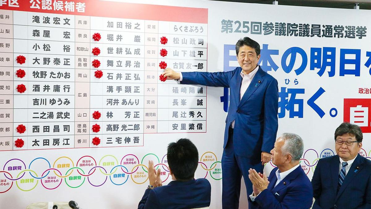 当選者に赤いバラをつける安倍。拍手するのは左から加藤、甘利、萩生田の面々。困った政治家ばかり。