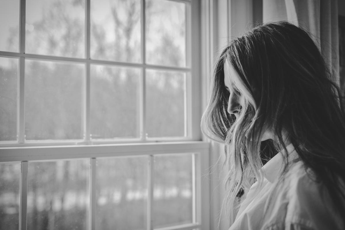 悲しそうに佇む女性の画像