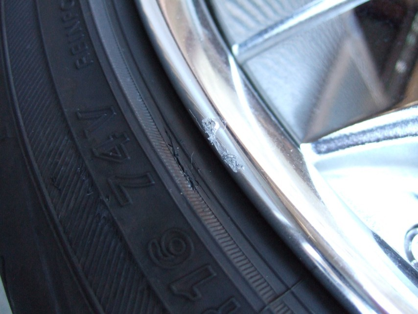 段差に乗り上げたために生じたタイヤの亀裂とリムのガリ傷