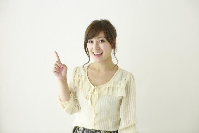 笑顔で人指し指を立てる女性