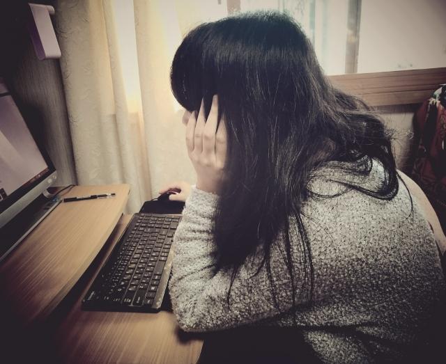 パソコンに向かう猫背の女性