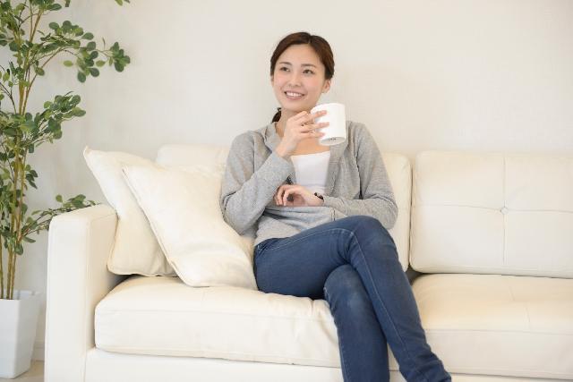 ソファで飲み物を飲む女性