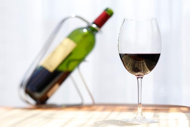 傾いたワインボトルとグラスに注がれたワイン