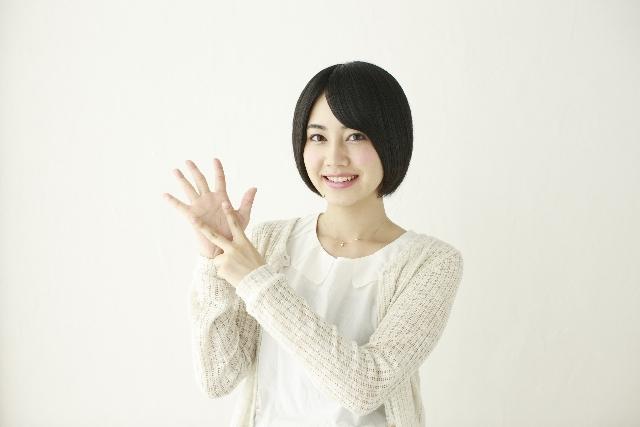 指で7を作る女性