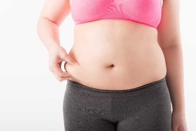 お腹の脂肪をつまむ女性