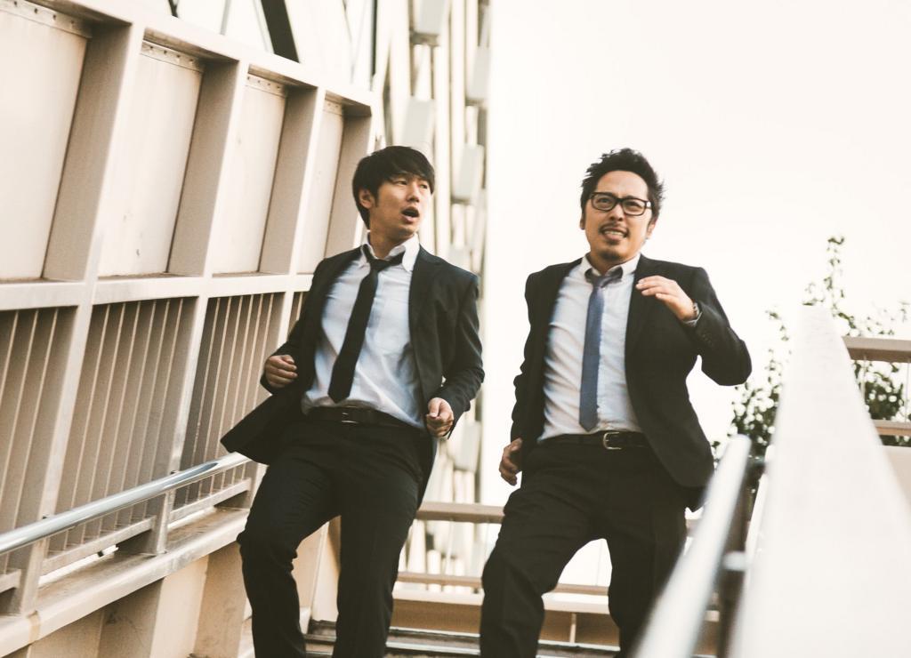 階段を降りるサラリーマンの男性二人