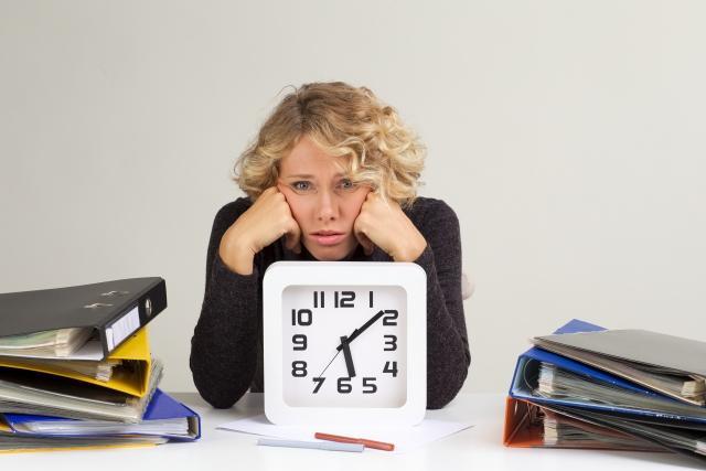 時計の前で悩む女性