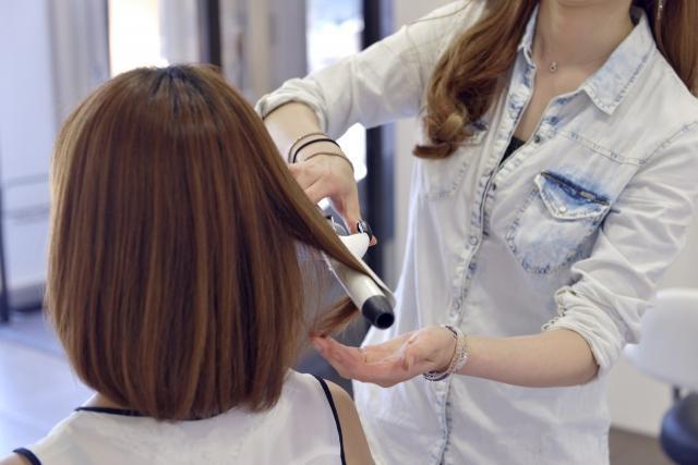 髪の毛をセットされる女性