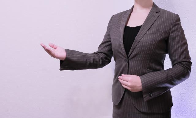 スーツを着た女性、ご案内ポーズ