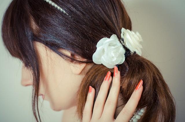 シュシュを付けた髪の毛に触れる女性