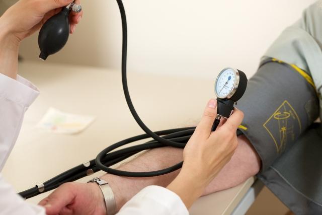 血圧を計る男性