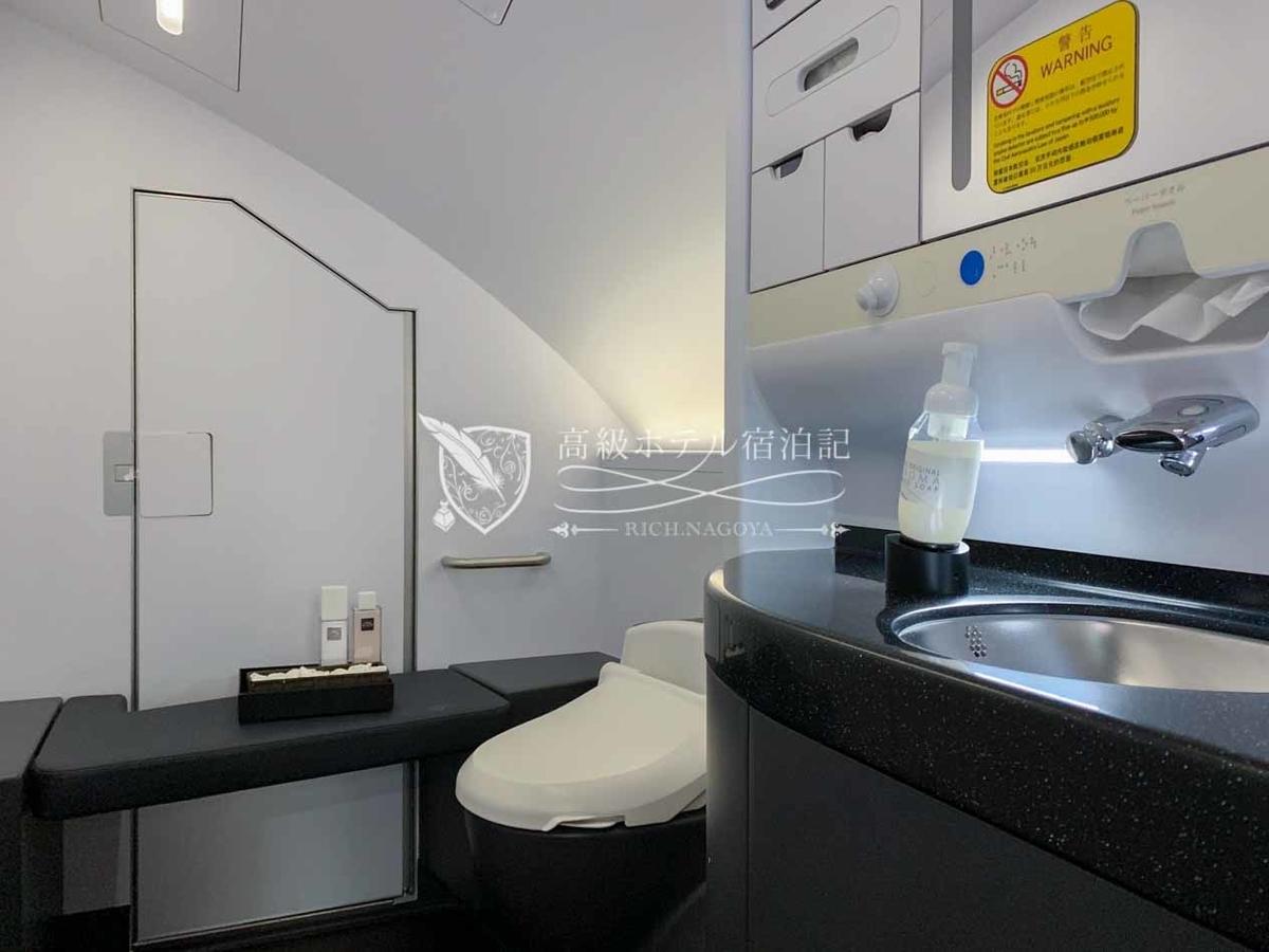 ANA-A380:トイレ 便器と洗面台のスペースが区分けされていて、奥にはベンチシートも設置されている。