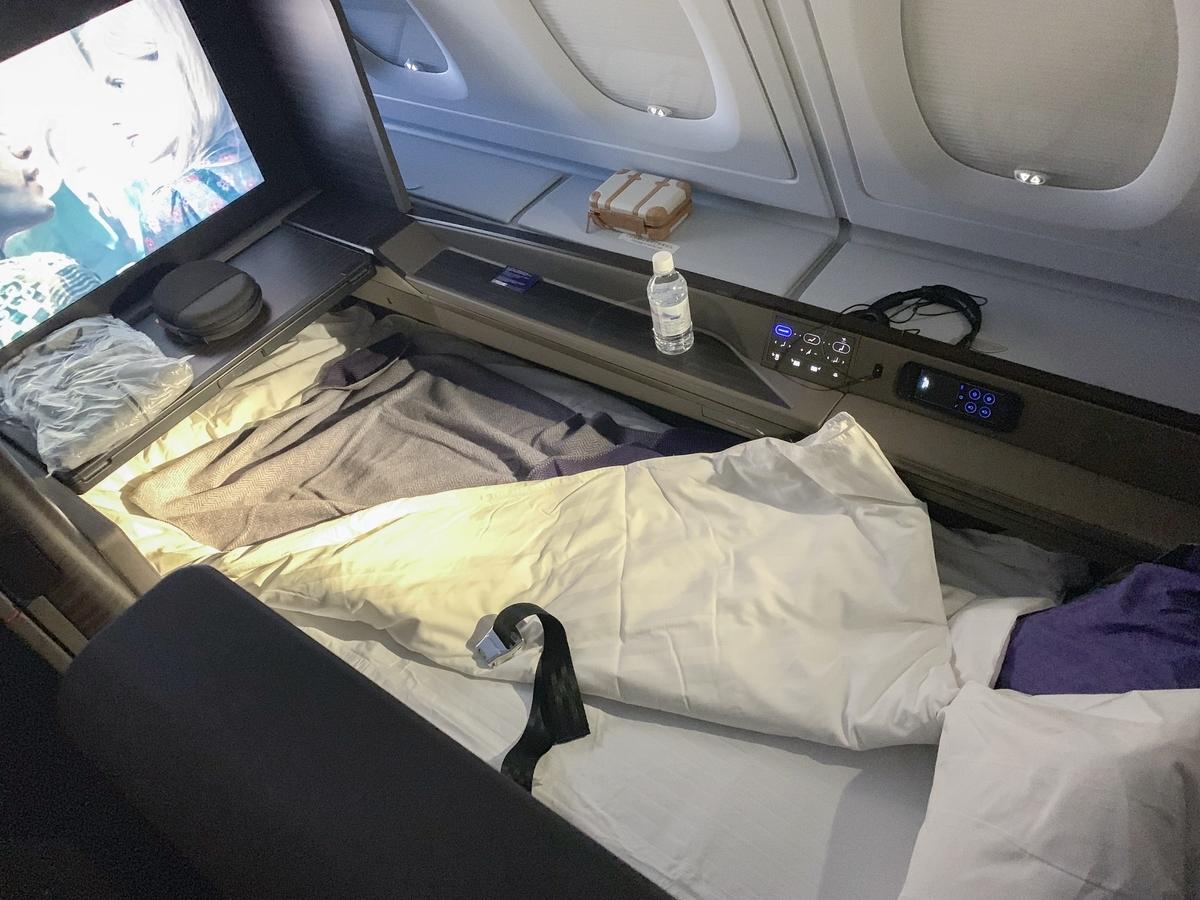 就寝時は客室乗務員がマットレスと掛布団を用意、ベッドメイクしてくれる。寝心地最高。