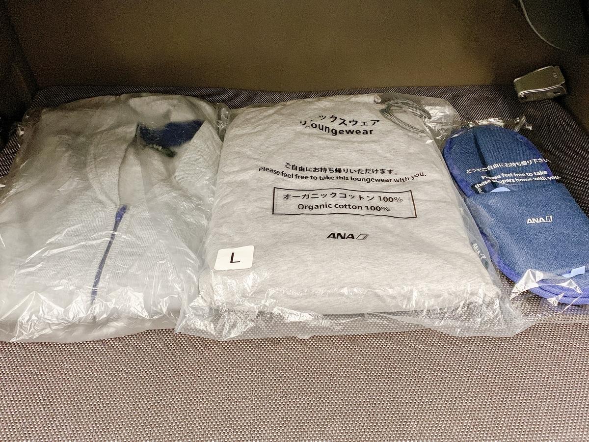 ファーストクラスの乗客には、カーディガン、2ピースパジャマ、スリッパを支給。2ピースパジャマはサイズあり。Lサイズを勧められて着てみたらブカブカ....