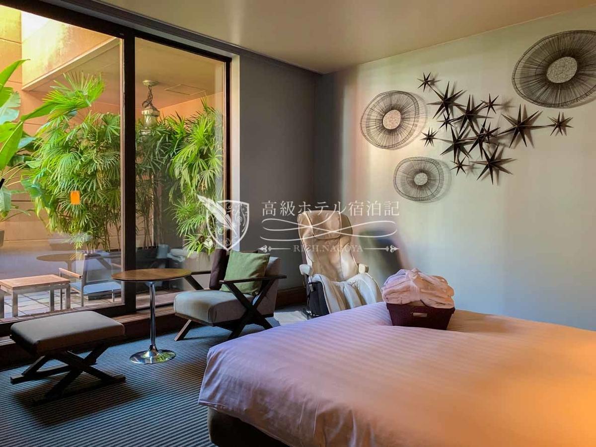 コーナーダブルクイーン(307号室/44.5㎡):角部屋に位置するワンルームタイプの客室。植物が生い茂るテラスと緑を基調とした室内は南国のリゾートホテルを彷彿とさせる。ベッドルームにはクイーンサイズベッド(160x200)の他、ビジネスデスク、ダイニングテーブルセット、マッサージチェアなどを用意。