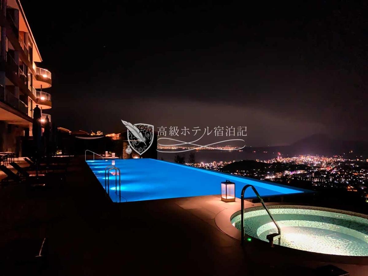 スタイリッシュなライトニングが施されたインフィニティプールから望む夜景
