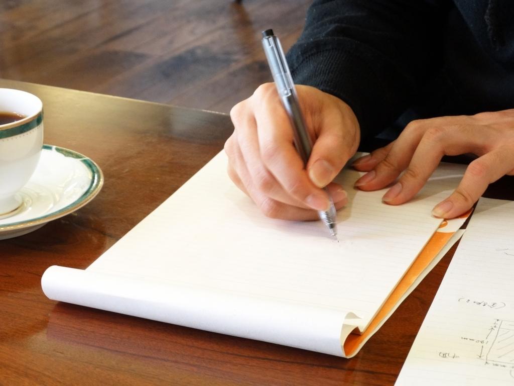 紙にペンで文章を書いている