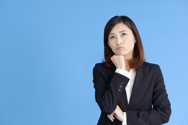 青い背景と悩んでいる女性