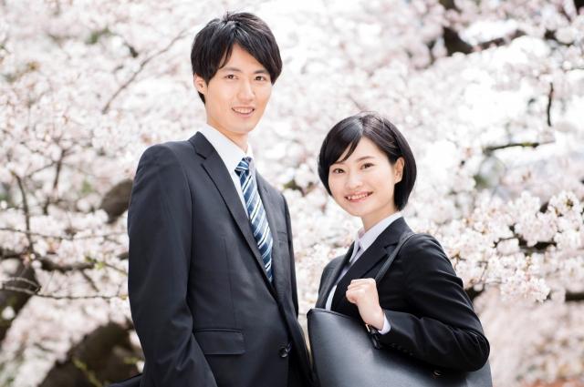 満開の桜の背景とスーツ姿の男女の上半身
