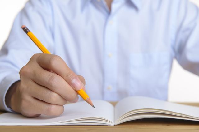 鉛筆でノートに書こうとしている青いシャツを着たヒトの胸