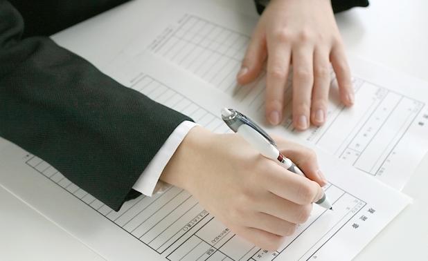 スーツを着た人が提出書類を書いている手元の写真