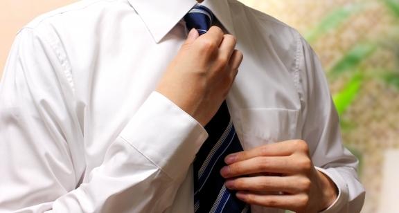 ワイシャツでネクタイを直す男性