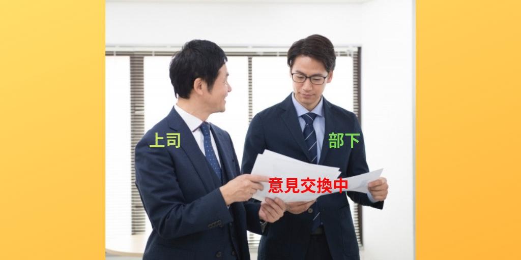 書類を見ながら立って議論するスーツ姿の二人の男性
