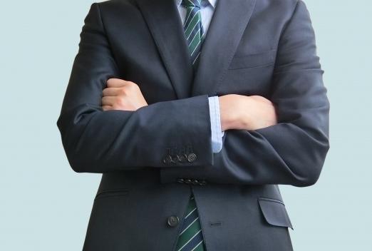 腕組みしたスーツ姿の男性の上半身