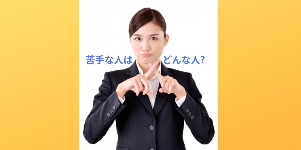 胸元で指でバツ印を作っているスーツ姿の女性の上半身
